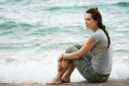 sad woman sitting by the ocean