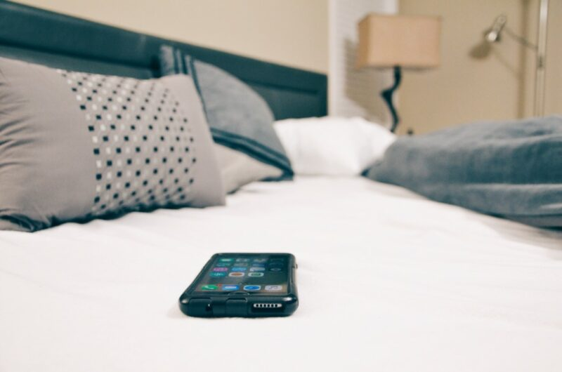 A phone on the bed to represent how to use it to track your luteal phase.